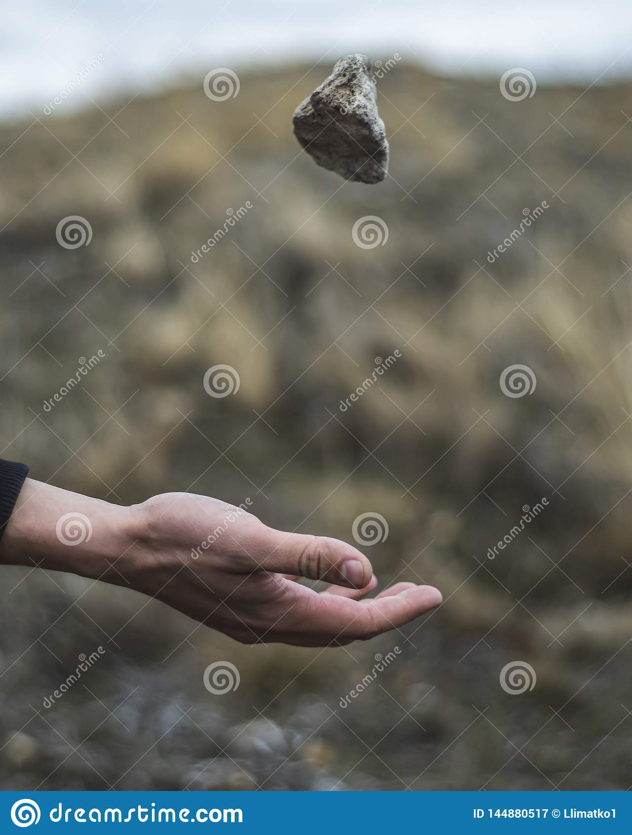 Stone hovering over the arm. A stone thrown into the air. Gravity