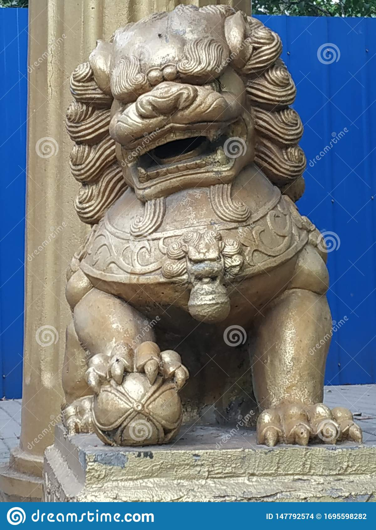 A stone lion is located next to the stone gate in the Euko Park