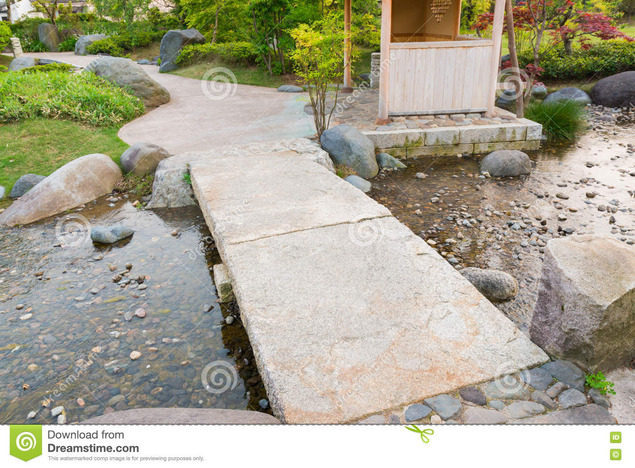 stone path in a japanese garden stone bridge across a pond stock photo