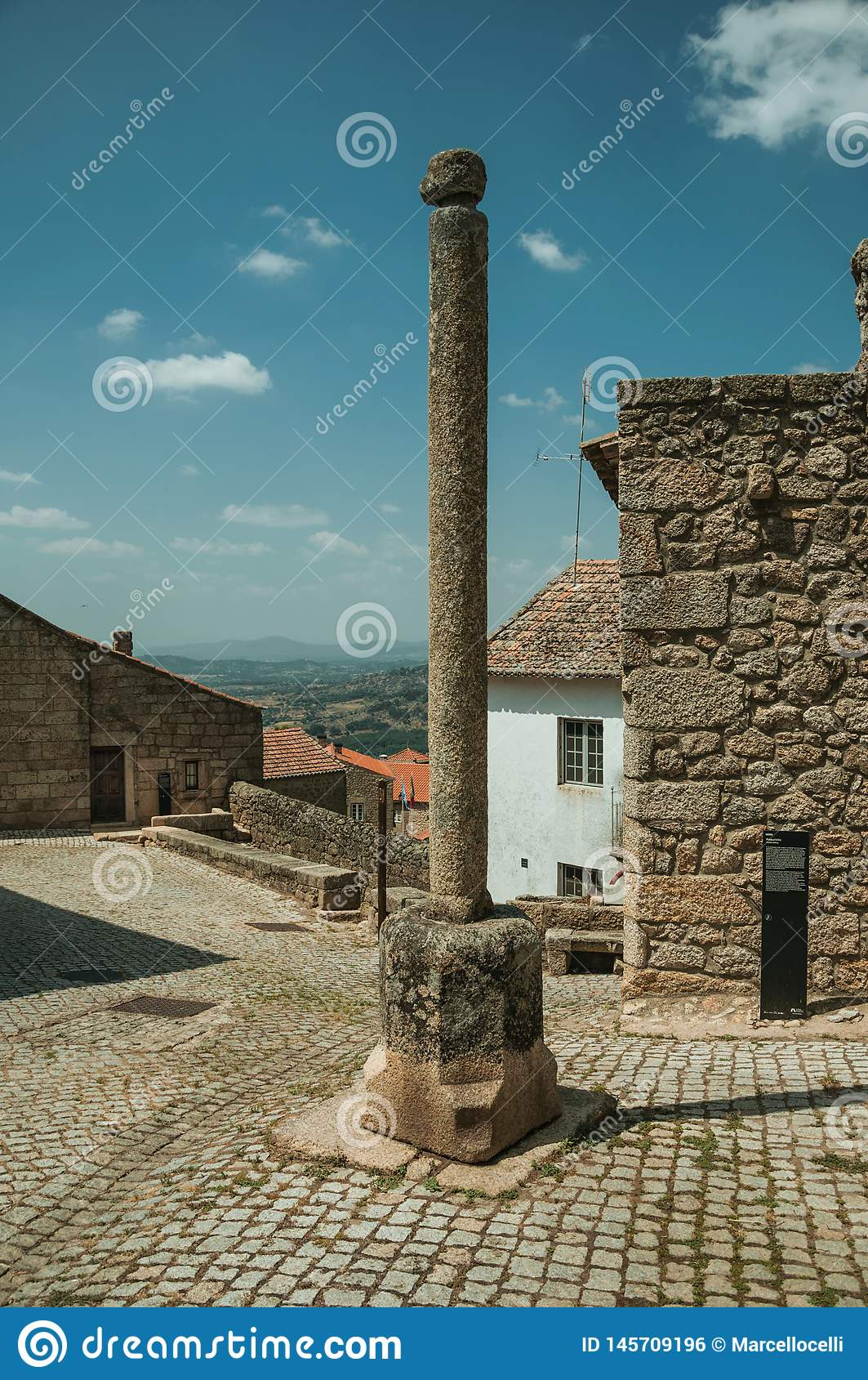 Stone pillory in front of old stone houses at Monsanto