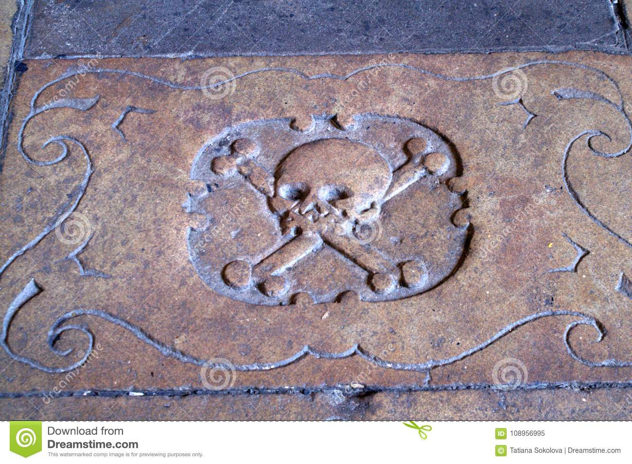 Skull And Two Crossbones. Frame Around The Image. Medieval Stone Carving.