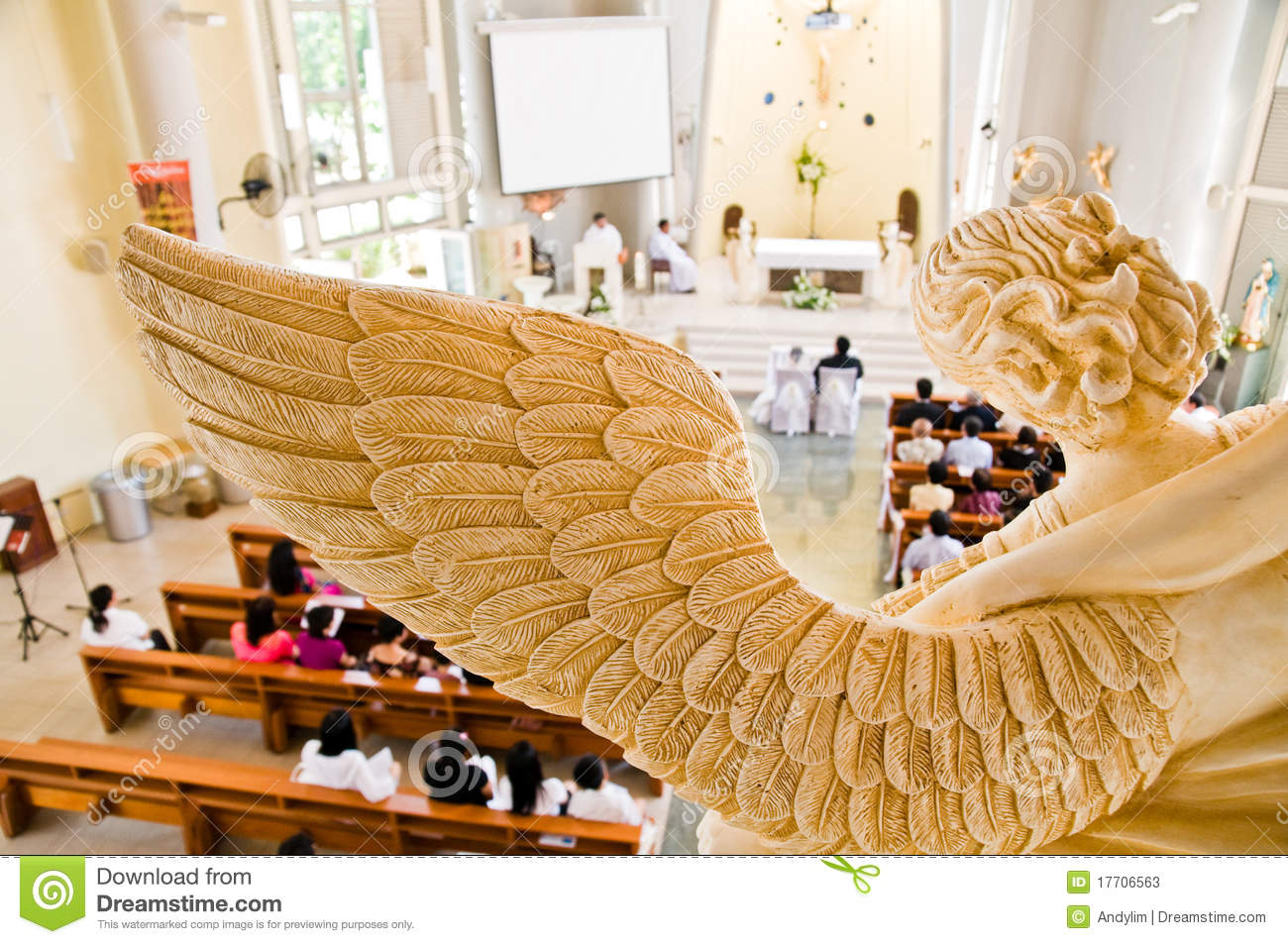 Stone statue of angel overlooking wedding ceremony