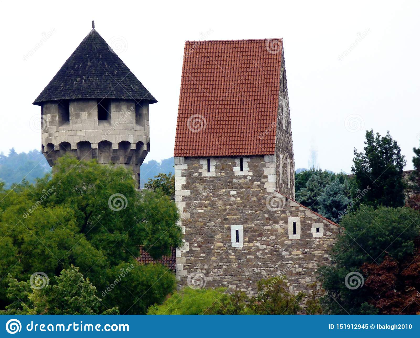 Stone Tower And Turret With Wooden Shingle Of Steep Sloped Roof