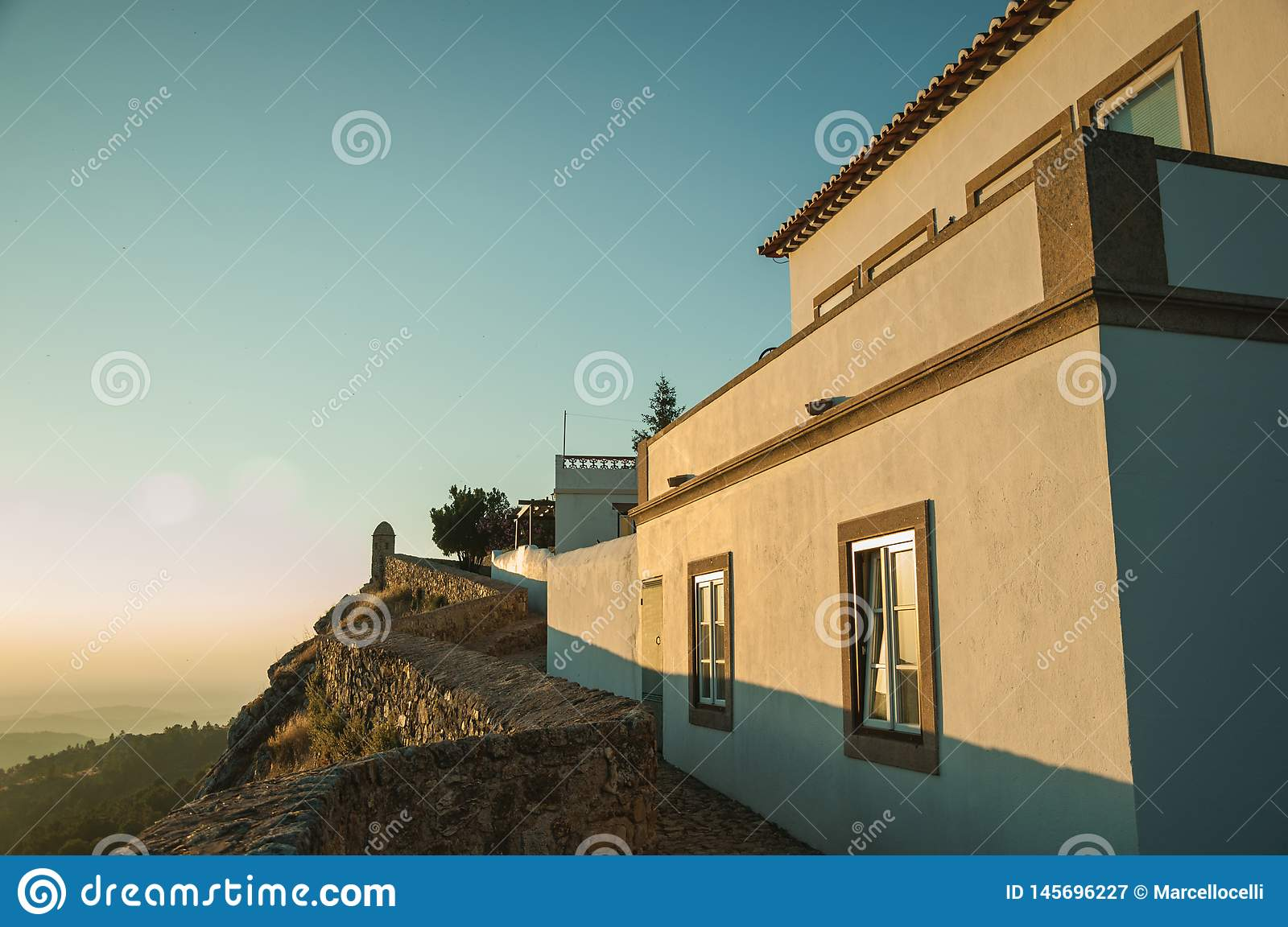 Stone wall and old house over rocky cliff in Marvao