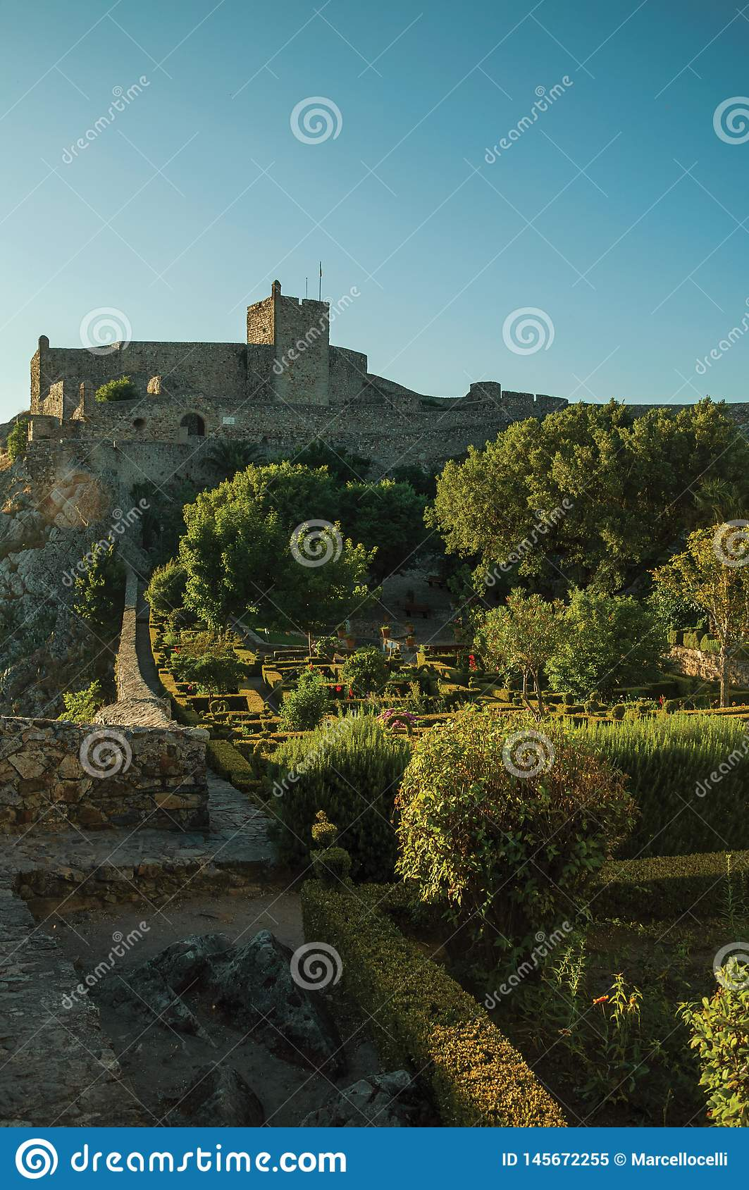 Stone walls and tower of Castle with lush flowered garden