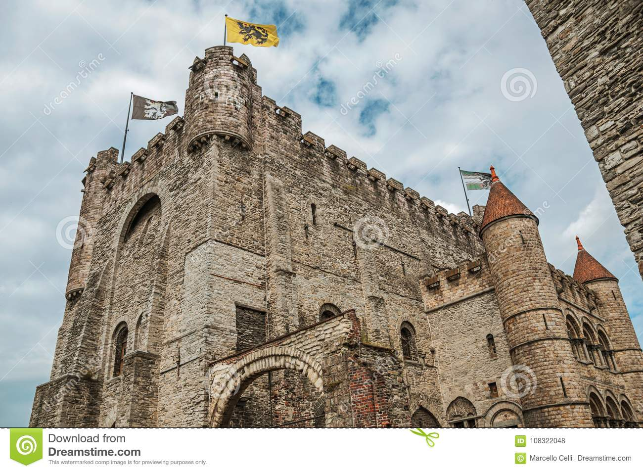 Stone watch-tower, walls and flags inside the Gravensteen Castle at Ghent.