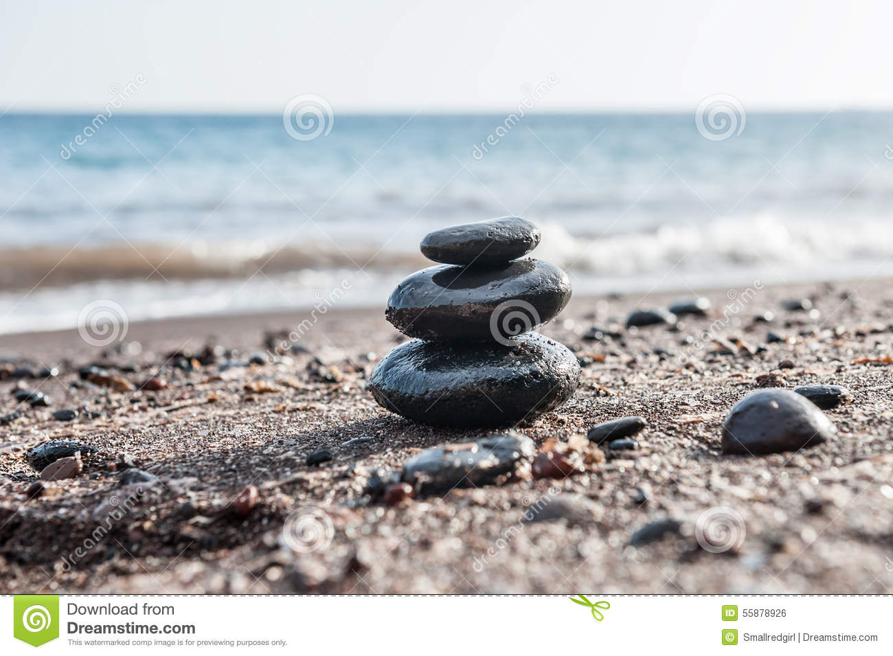 Stones pyramid on the beach, sea in the background