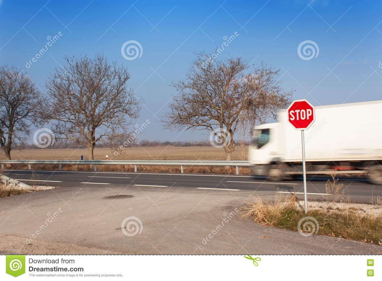 Stop Sign at Crossroads. Rural road. Exit onto the main road. Main road. Dangerous road. Traffic signs stop.