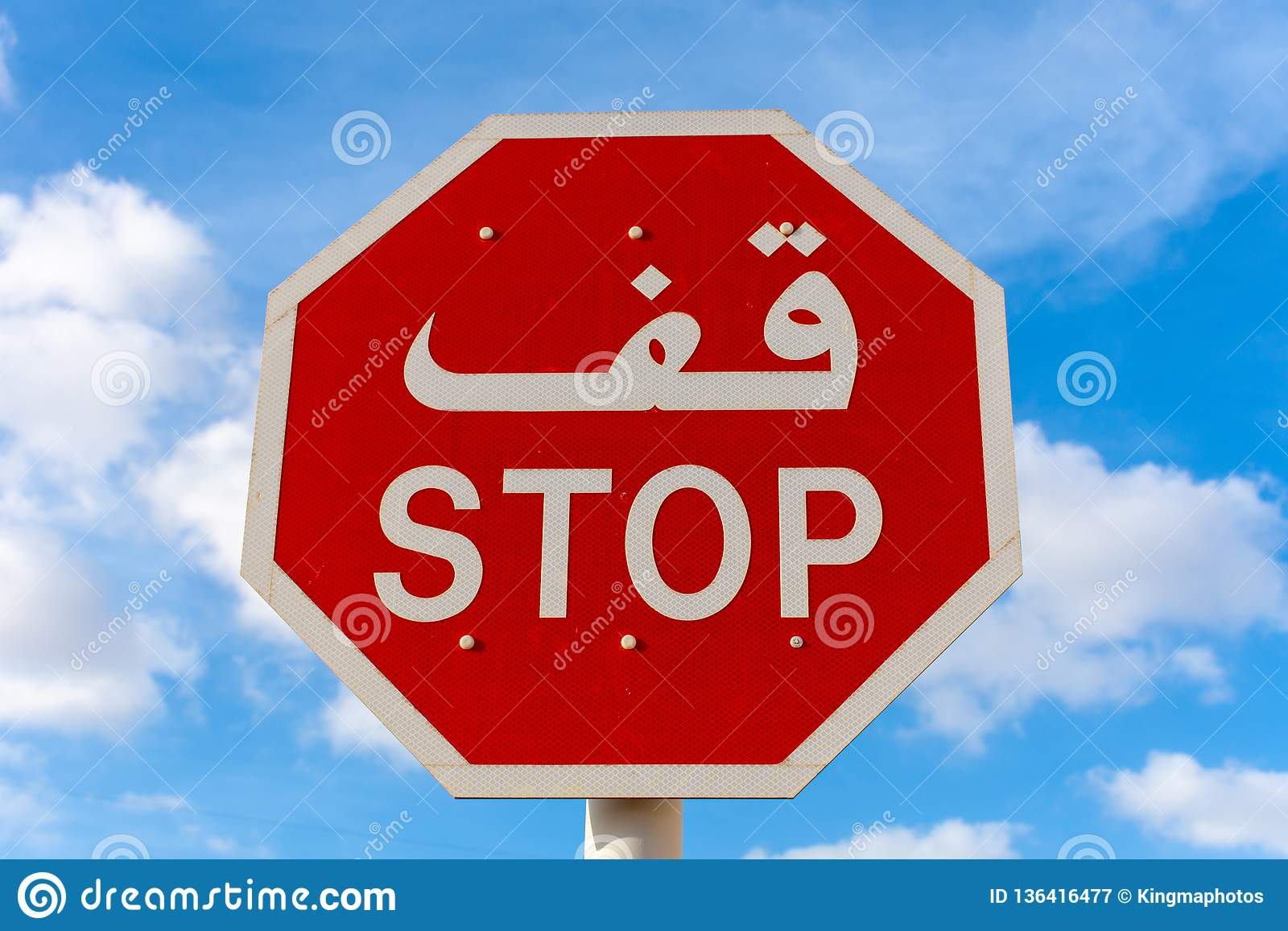 Stop sign in English and Arabic with blue sky and clouds in background.