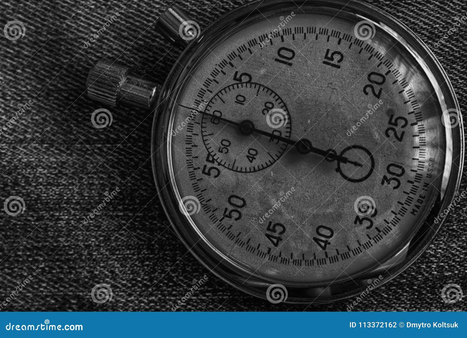 Stoppuhr auf abgenutzten Jeans Hintergrund, Wertmaßzeit, alter Uhrpfeilminute und zweiter Genauigkeitstimer-Aufzeichnung
