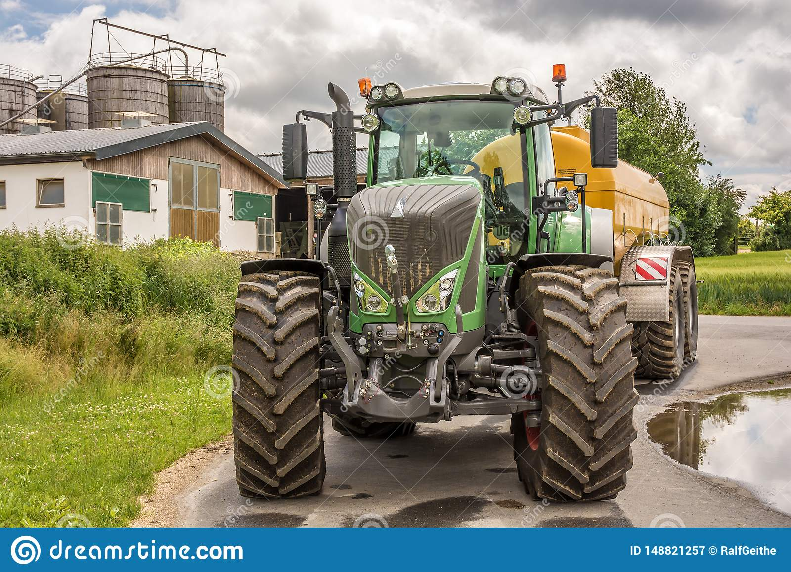 Stor bastant traktor med lantgården i bakgrunden