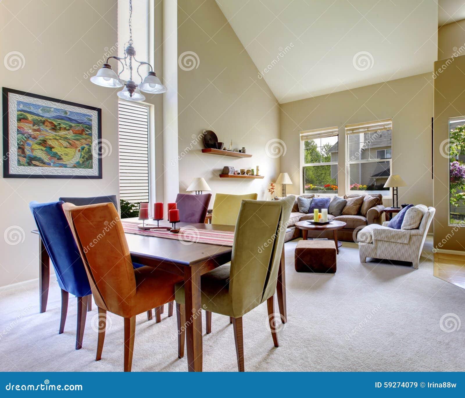 Stor beige ljus vardagsrum med matsaltabellen med olika färgstolar ...