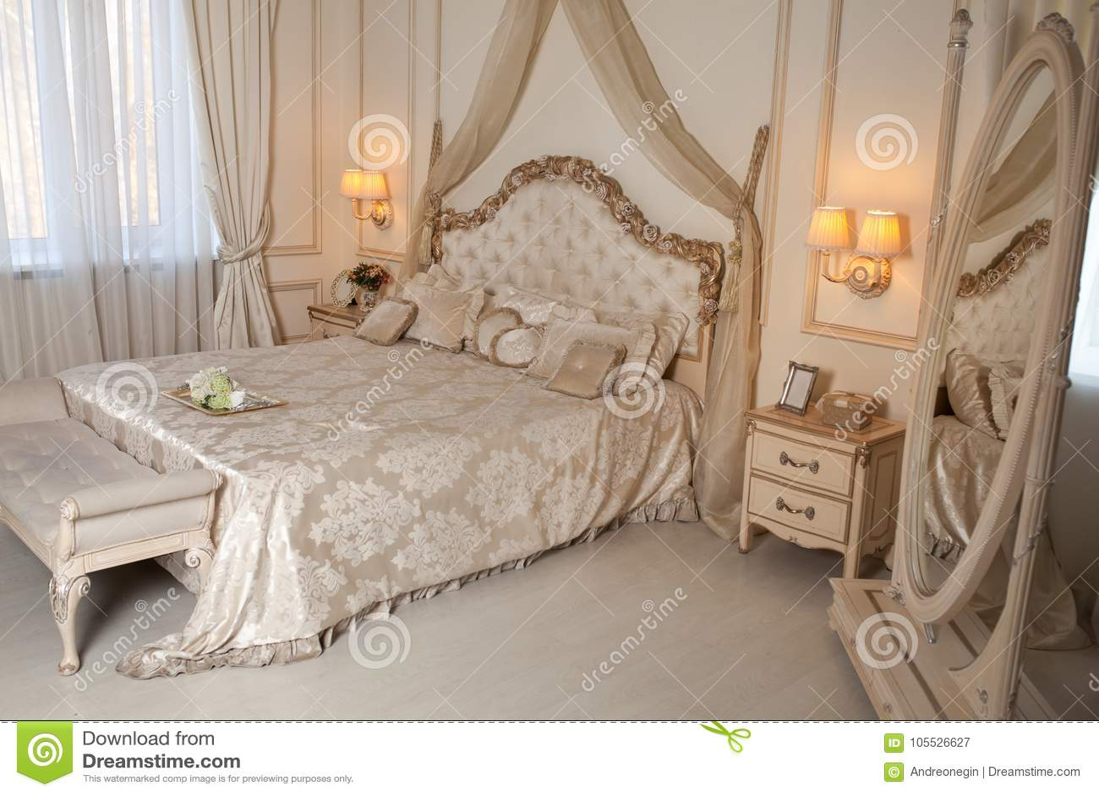 Stor bekväm dubbelsäng i elegant klassiskt sovrum