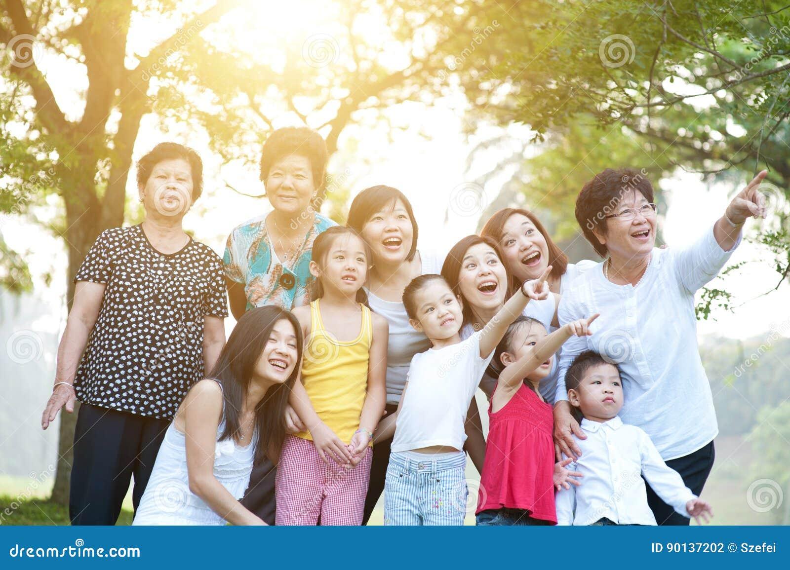 Stor grupp av den asiatiska mång- utvecklingsfamiljen som har utomhus- gyckel