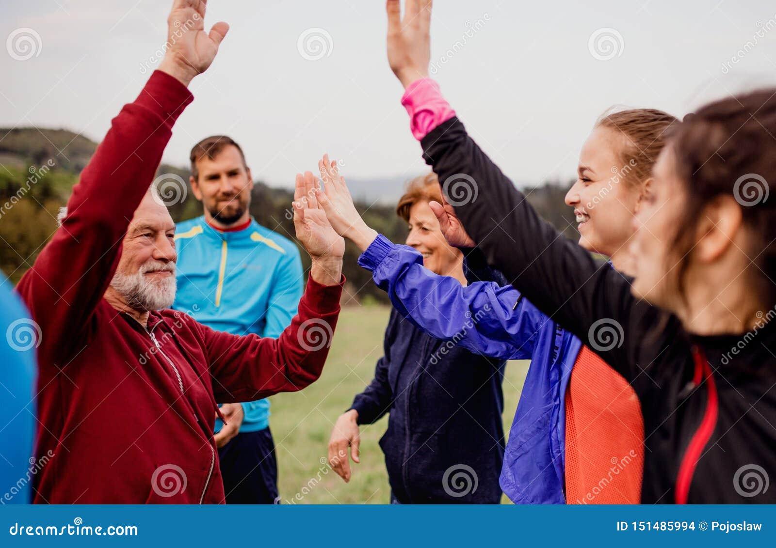 Stor grupp av passformen och aktivt folk som vilar, når att ha gjort övning i natur