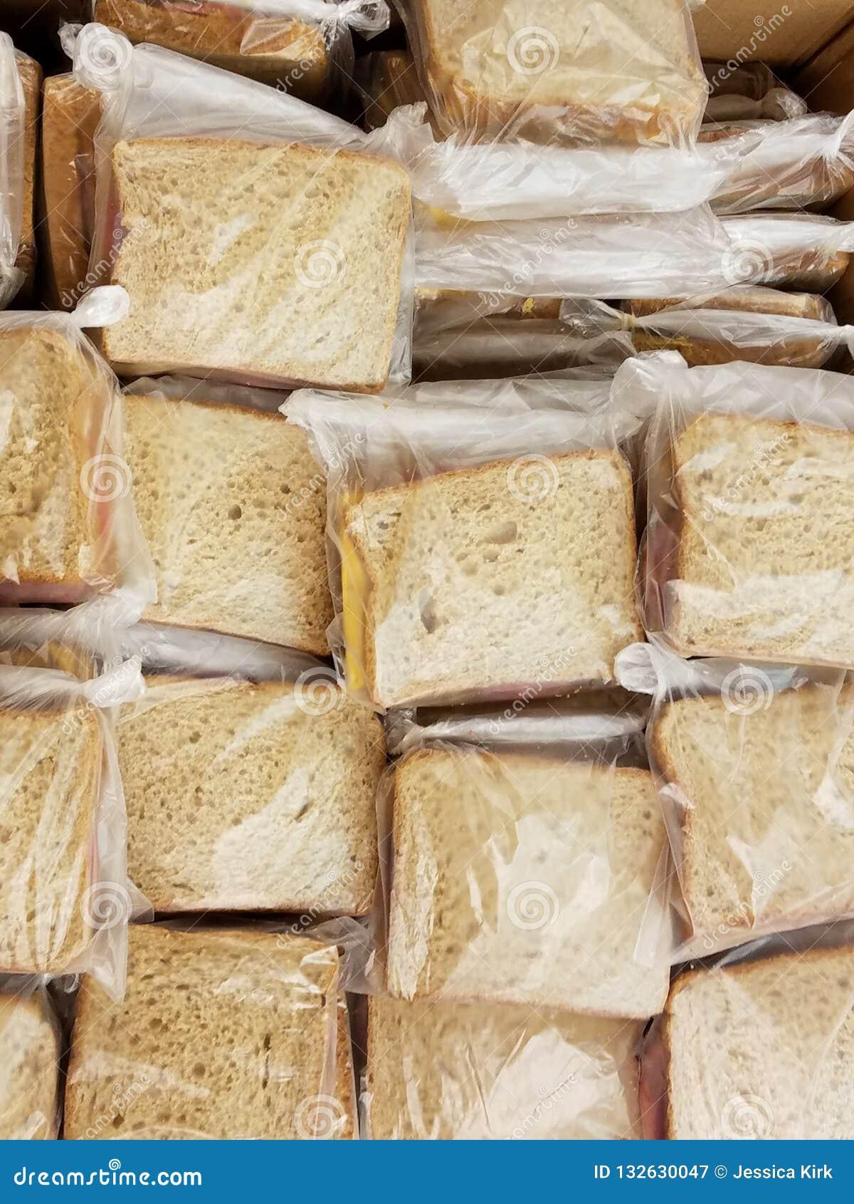 Stor grupp av smörgåsar på vetebröd som förbereds för det hungrigt