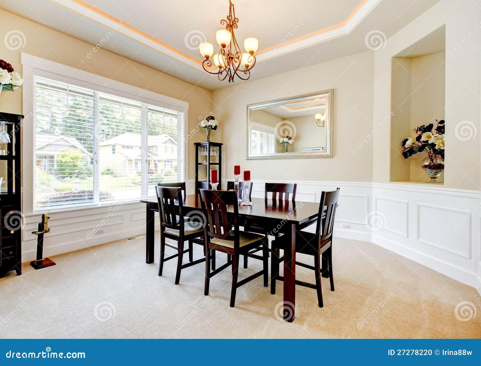 Stor lyxig matsal med mörkt wood möblemang.