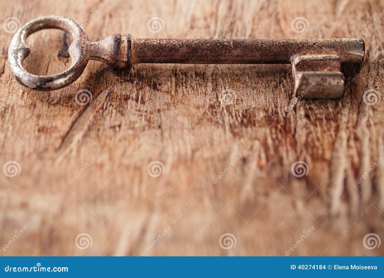 Stor rostig tappningmetalltangent på gammal träbakgrund