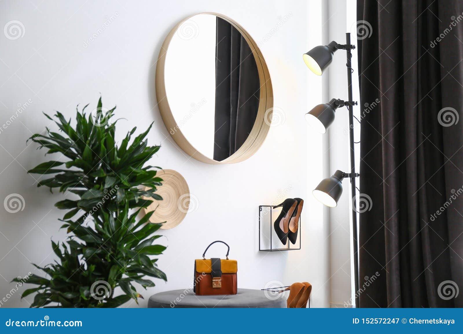 Stor rund spegel, houseplant och dekor nära den vita väggen i hall