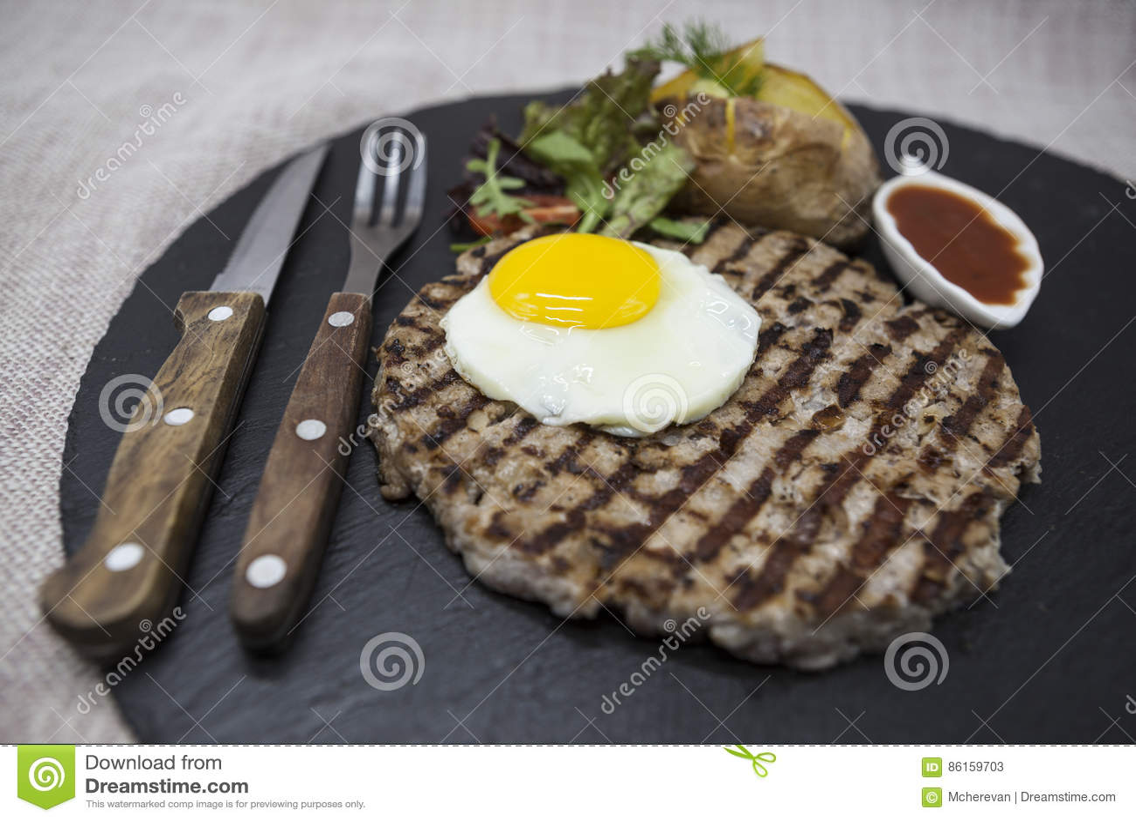 Stor, saftig läcker stek med ett stekt ägg och bakade potatisar på en stenplatta
