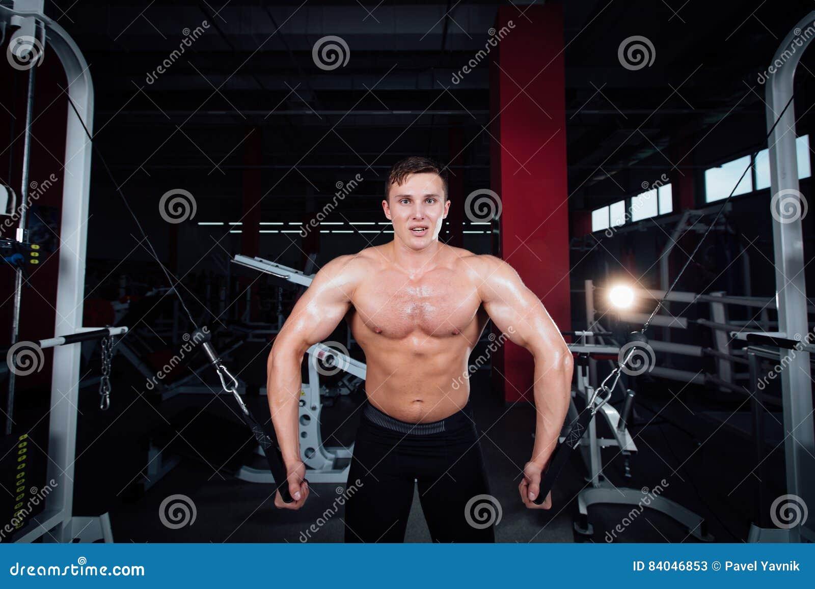Stor stark bodybuider utan skjortor visar övergångsövningar De bröst- musklerna och den hårda utbildningen