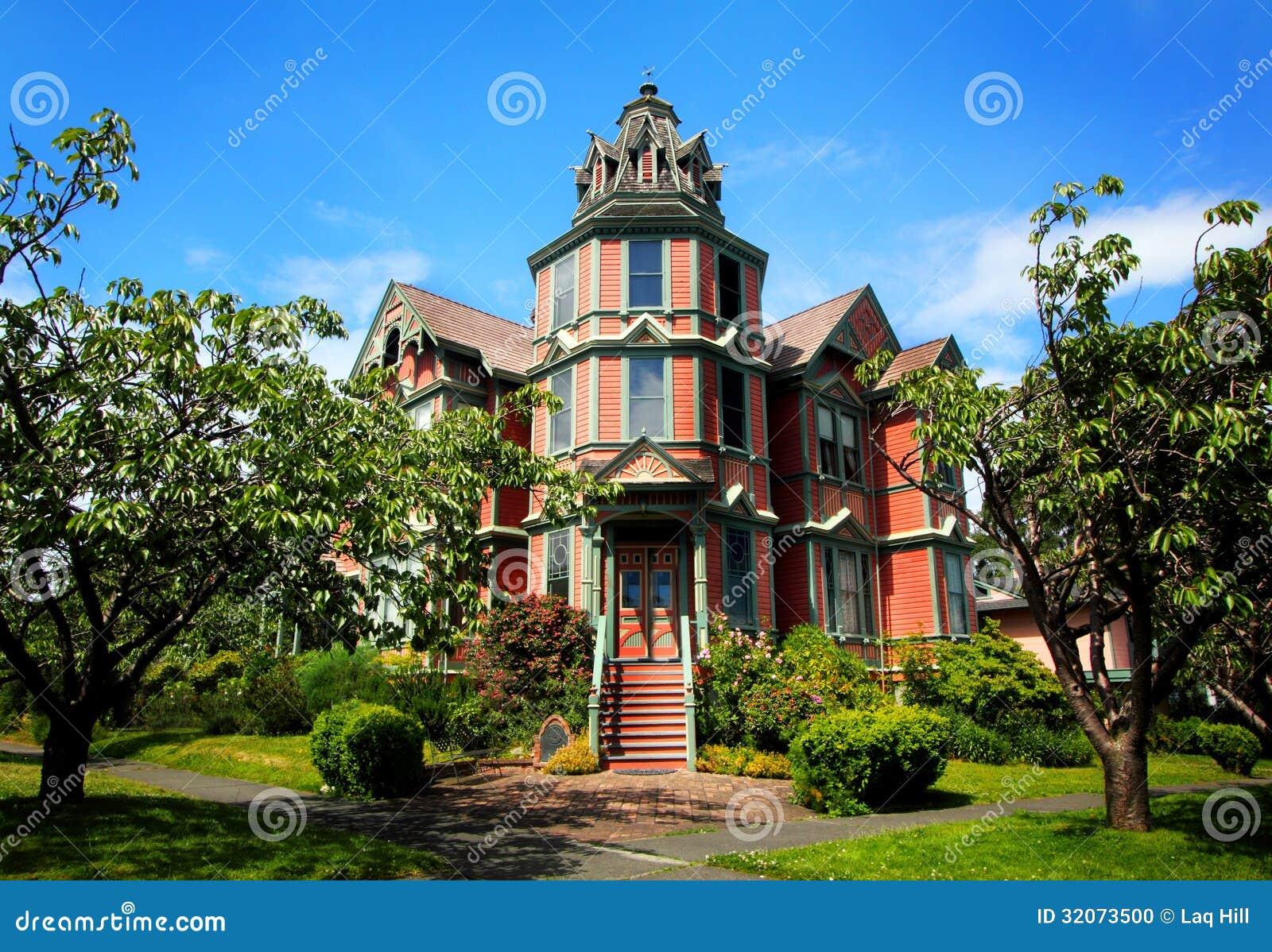 b1b60e41 Gatasikt av ett härligt stort gammalt lyxigt victorianhem med massor av  pepparkakaklippning, ett torn och många fönster under blåa himlar.