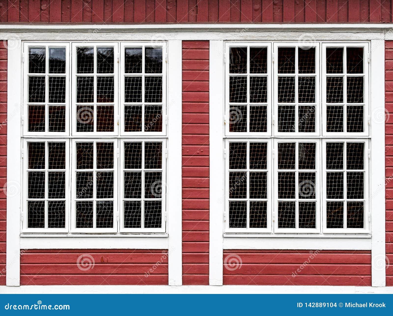 Stora fönster på en röd trävägg