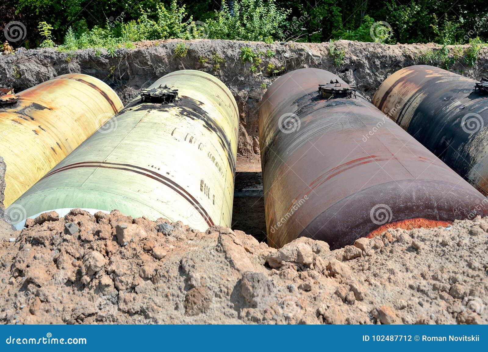 Stora metallbehållare begravas i jordningen i produktionlagret