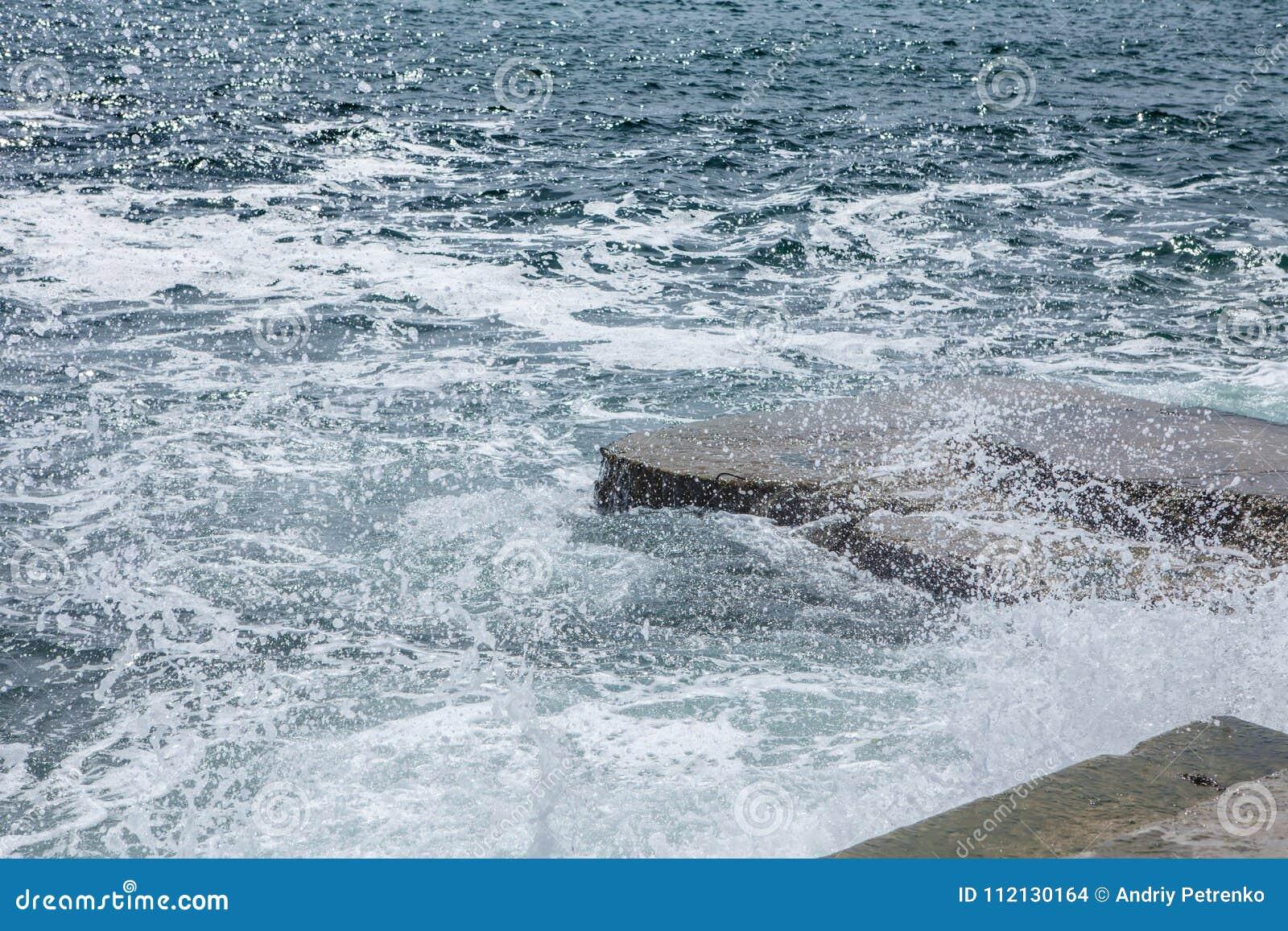 Stora vågor på det steniga kust- och blåtthavet
