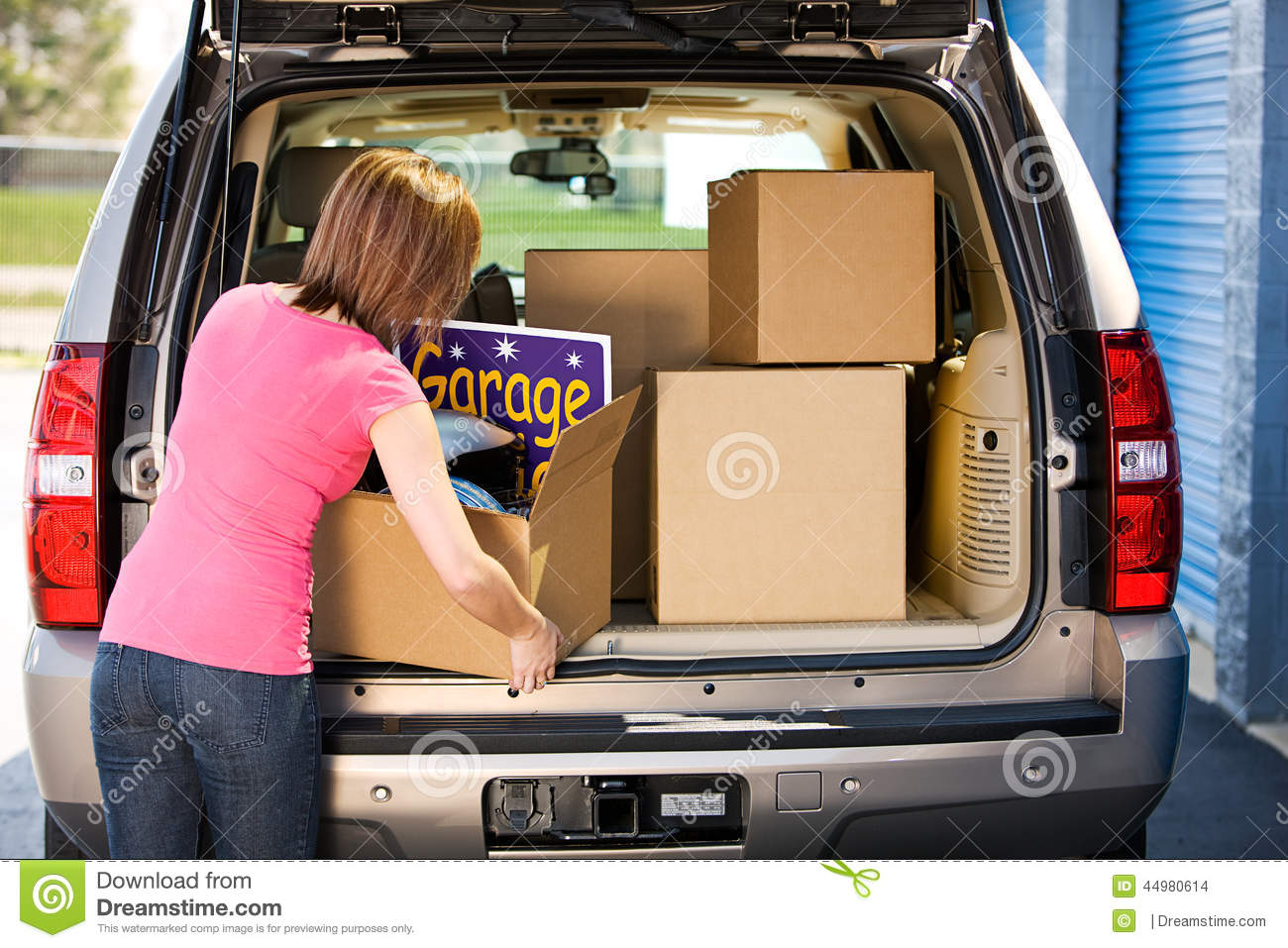 Storage: woman packing away garage sale leftovers stock photo ...