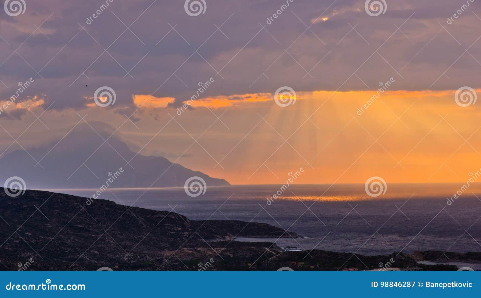 Stormachtige hemel en zonsopgang bij heilige berg Athos