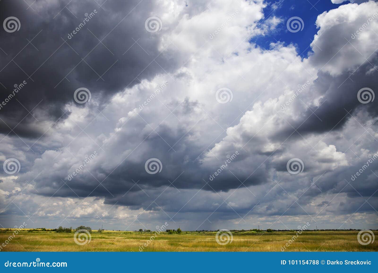 Stormig molnig himmel över slätten