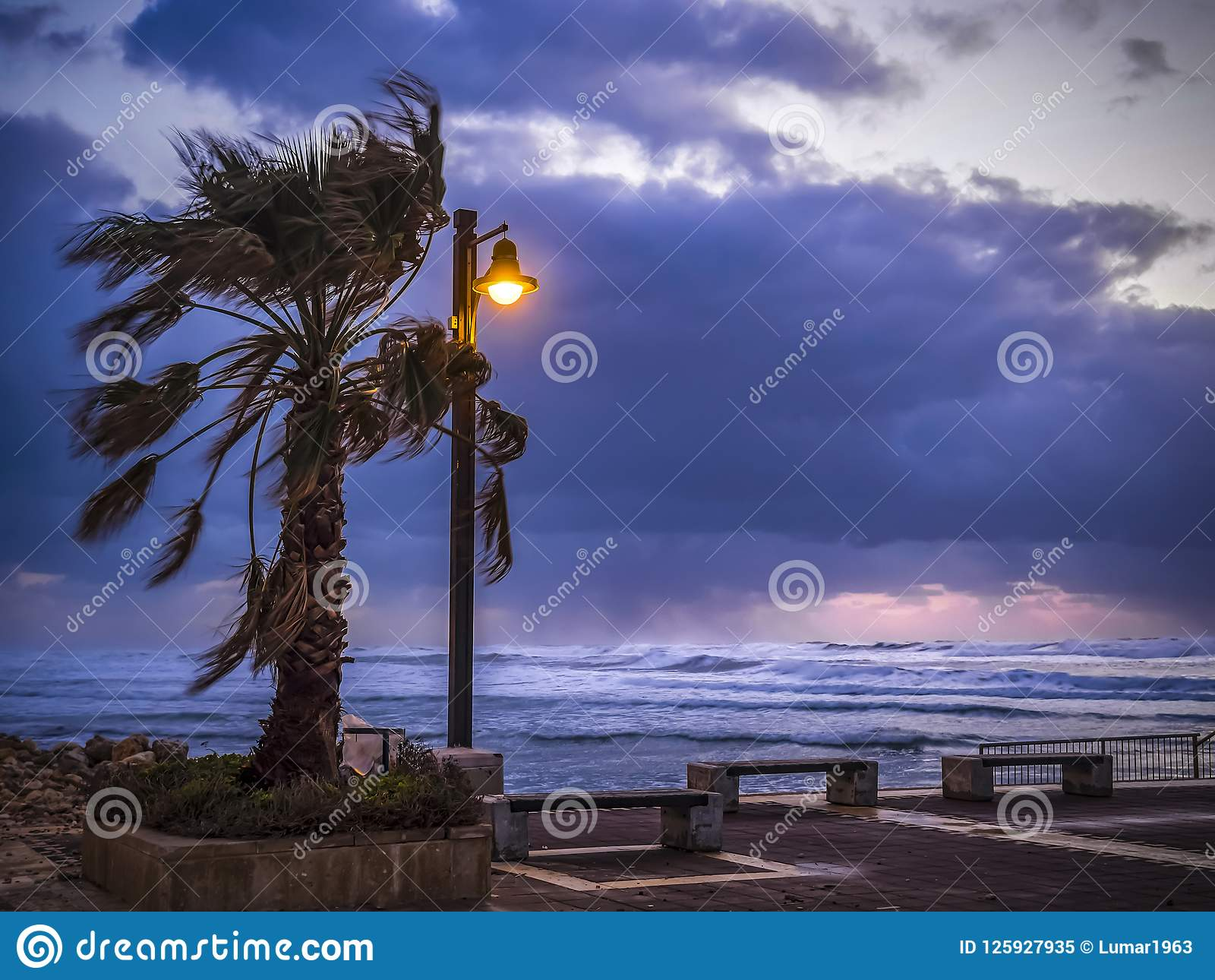 Stormy wind weather on the shores of the Mediterranean Sea, twilight, burning lantern.