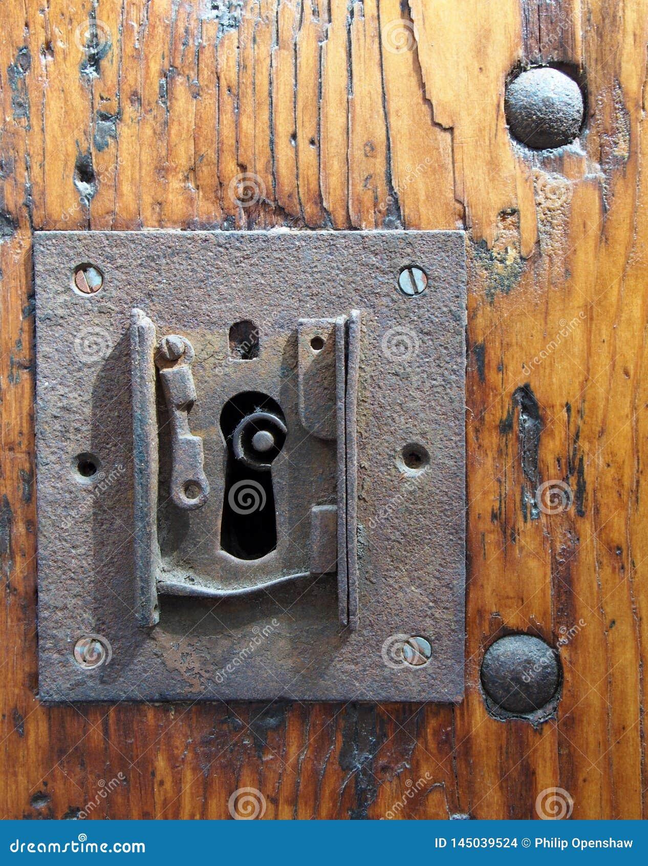 Stort fyrkantigt rostigt järnlås med nyckelhålet i en gammal lackad trädörr med slutet av de nyckel- synliga och metallnitarna