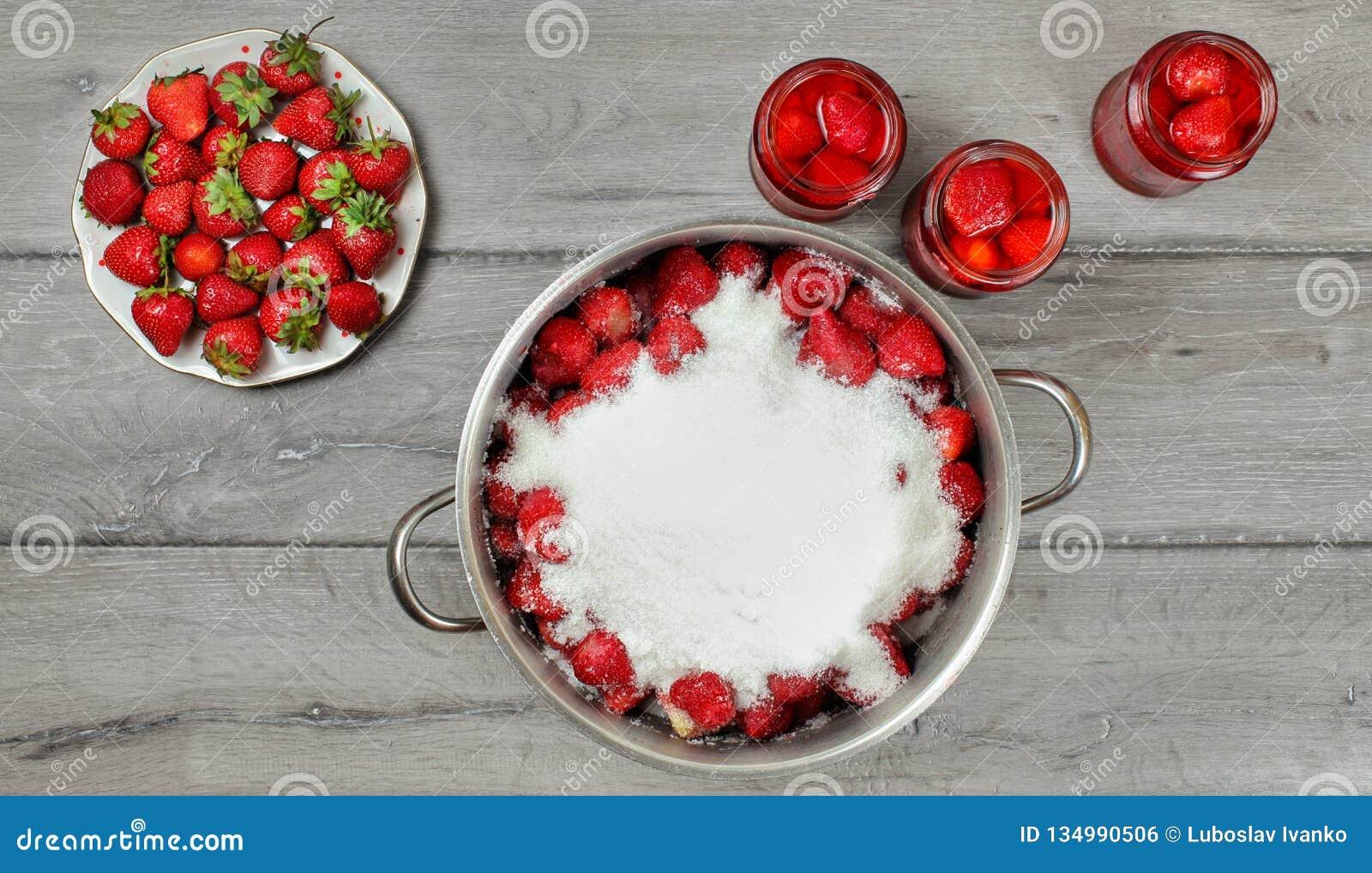 Stort Tabletop foto - stålsätta krukan av jordgubbar som täckas med den kristallsocker, plattan och glasflaskor med mer frukter o