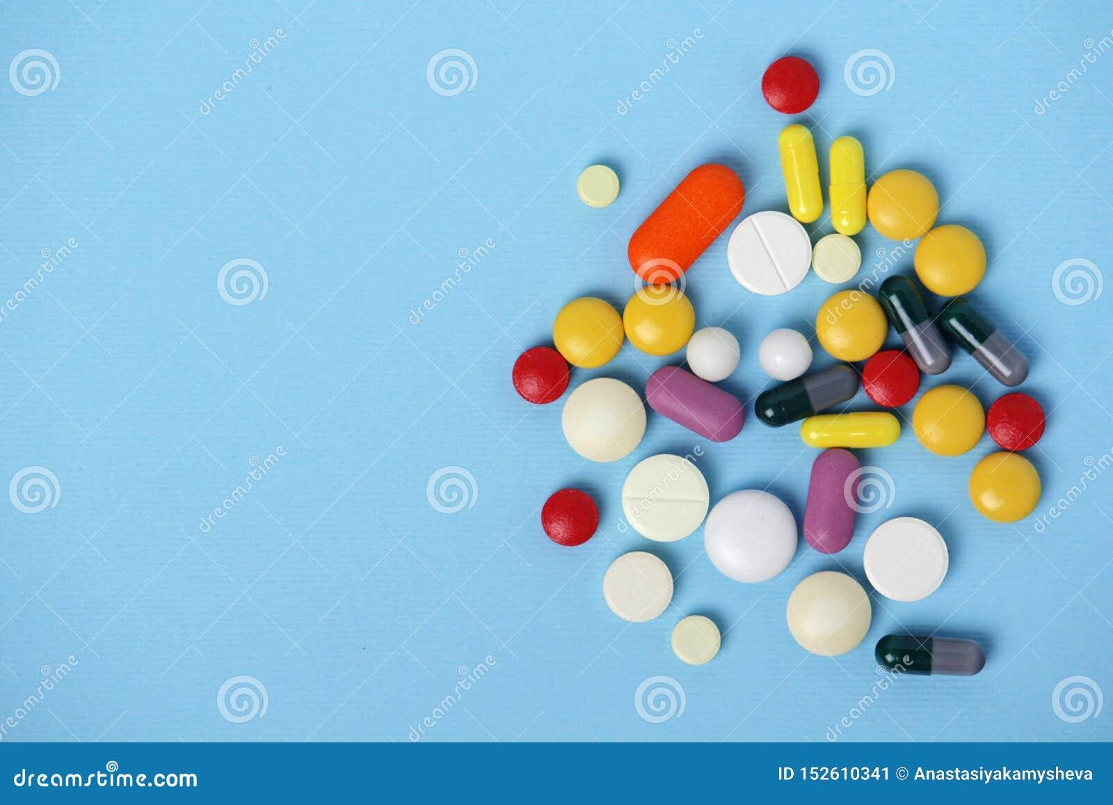 Stos kolorowe medycyny przy błękitnym tłem