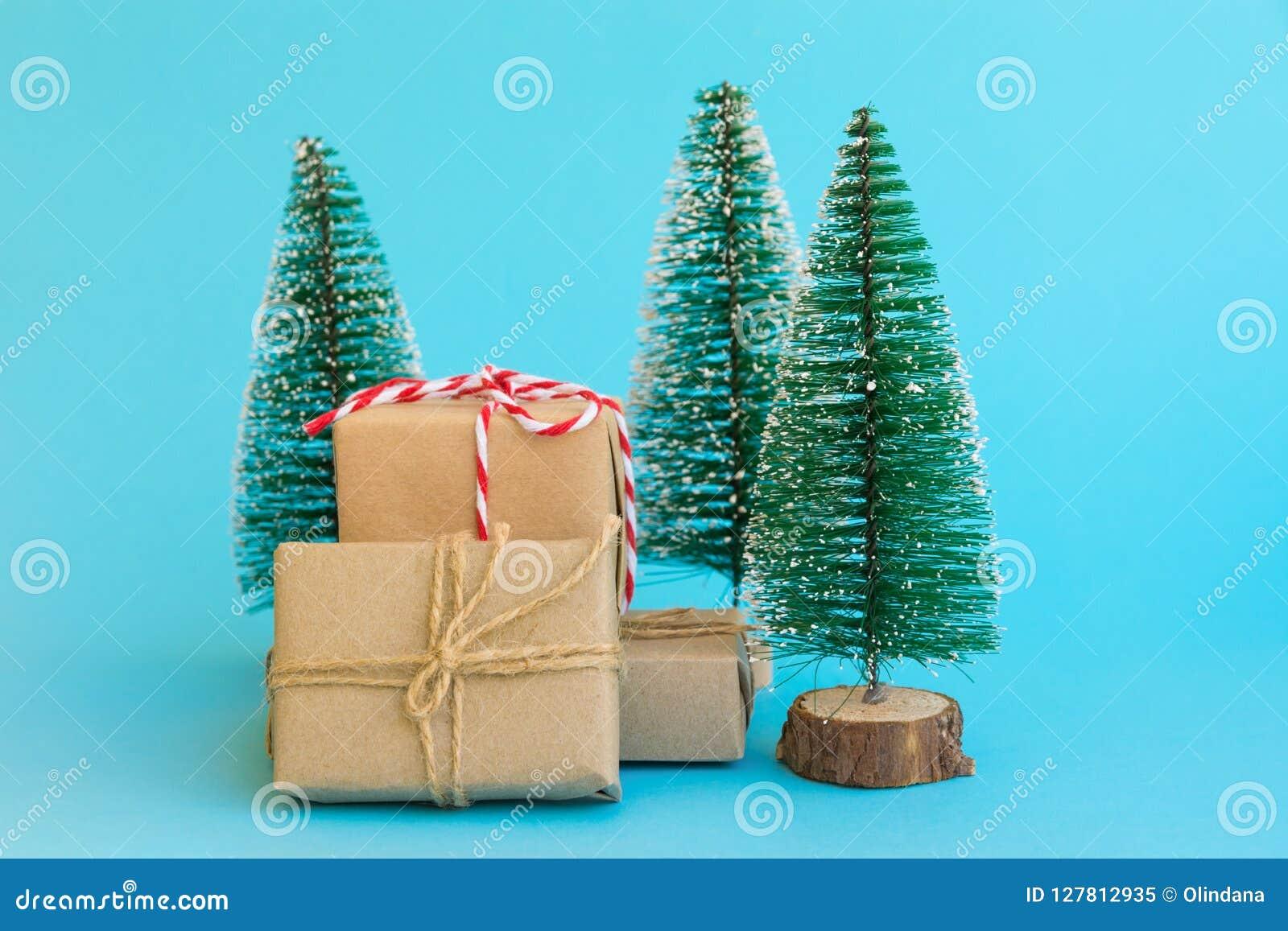Stos prezentów pudełka zawijający w rzemiosło papierze wiązał z dratw czerwonymi białymi tasiemkowymi choinkami na nowym błękitny