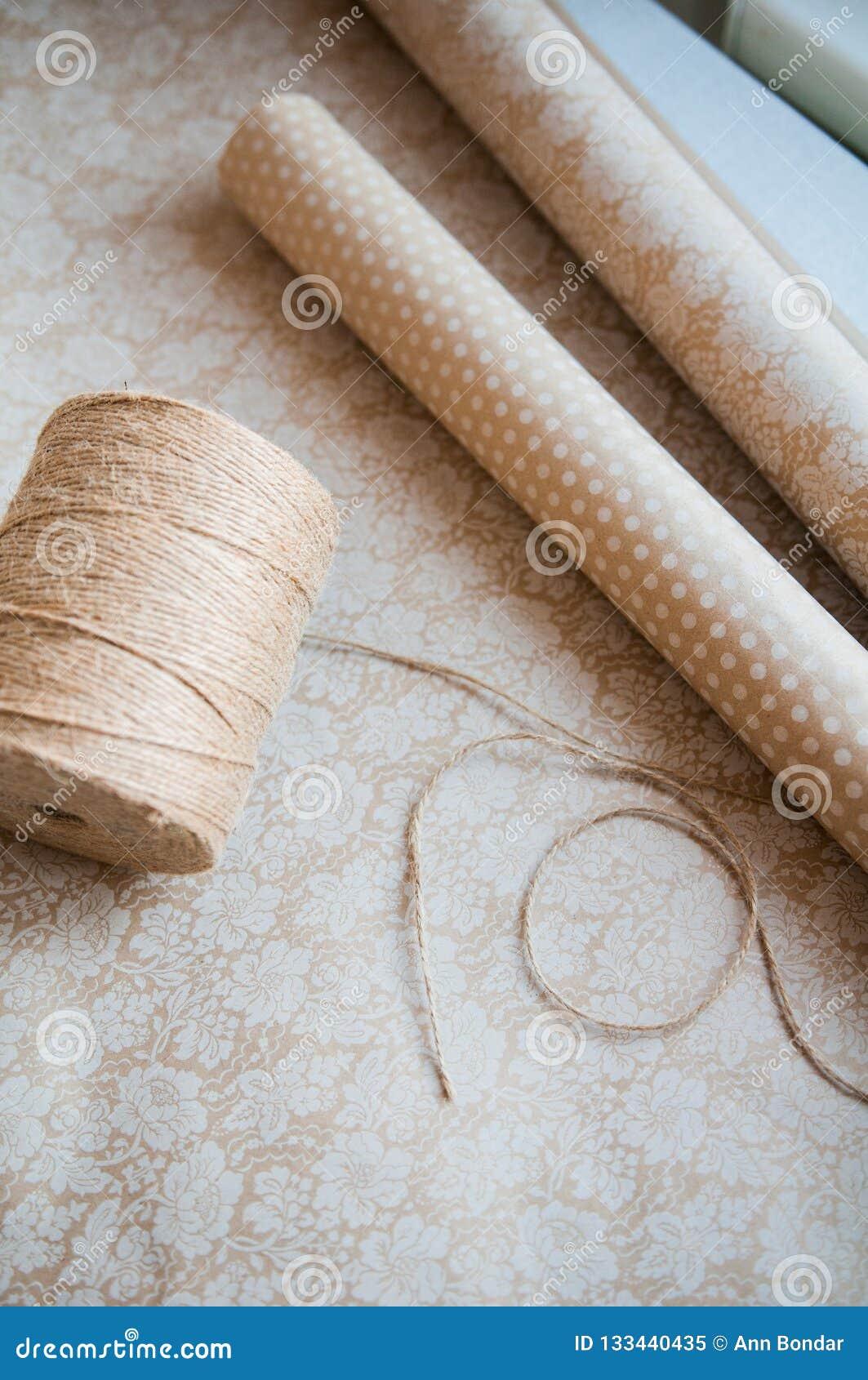 Stränga eller tvinna bundet i en pilbåge på bakgrund för kraft papper