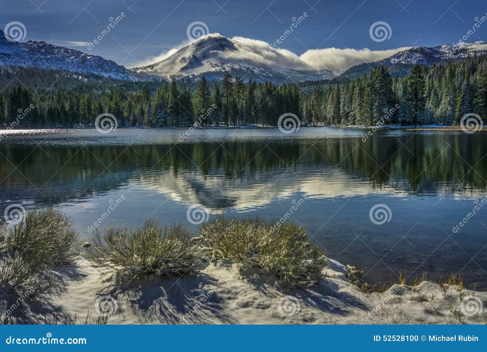 Sträuche und Lassen ragen nach Schneesturm mit Reflexionen im Manzanita See, Lassen vulkanischer Nationalpark empor