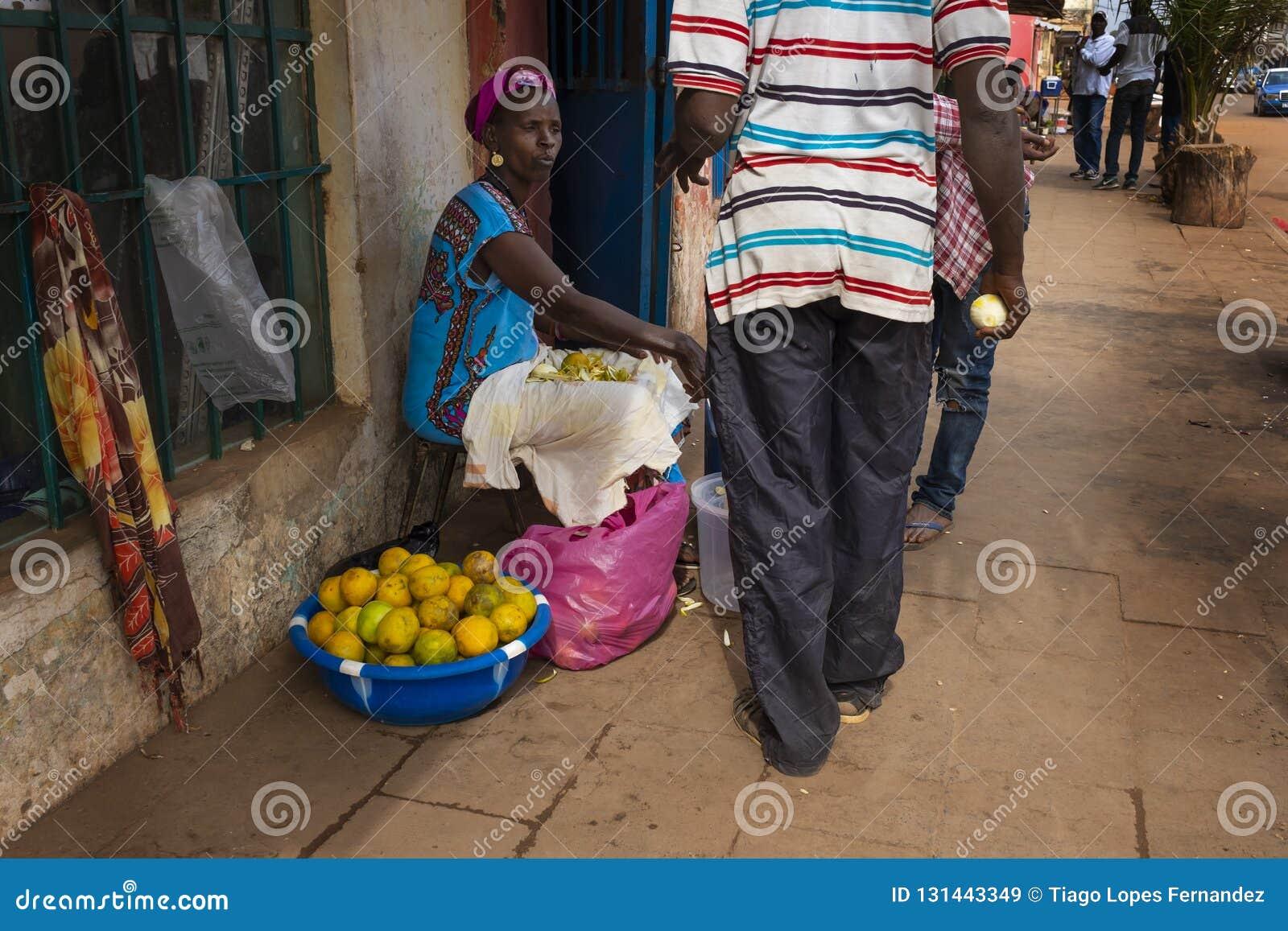 Straßenbild in der Stadt von Bissau mit einer Frau, die Orangen, in Guinea-Bissau, West-Afrika verkauft