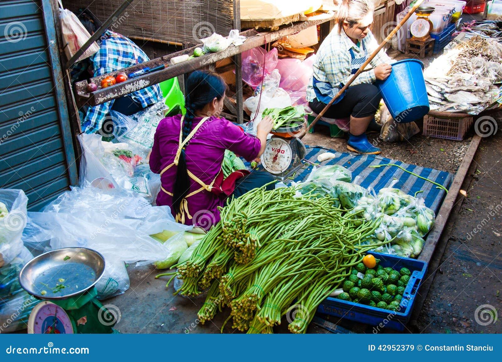 Straßenhändler auf berühmtem Maeklong-Eisenbahn-Markt Wann immer ein Zug sich nähert, die Markisen und das s
