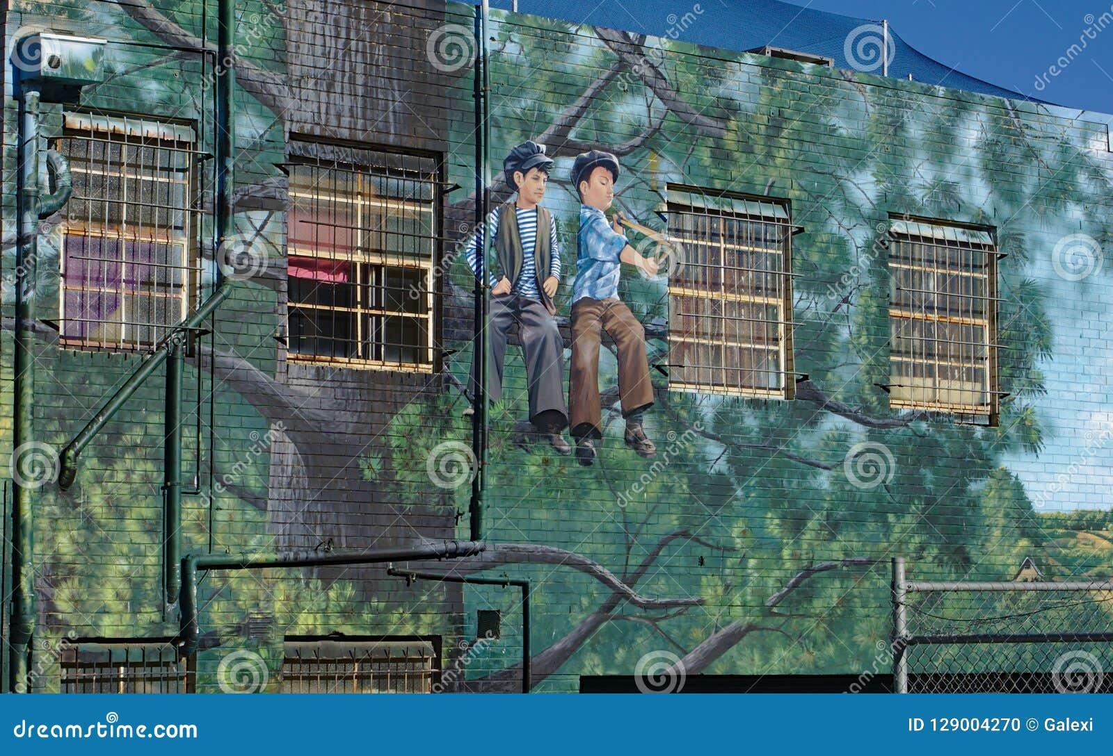 Straßenkunst von zwei Jungen, die auf Baum bei Frankston, Australien sitzen