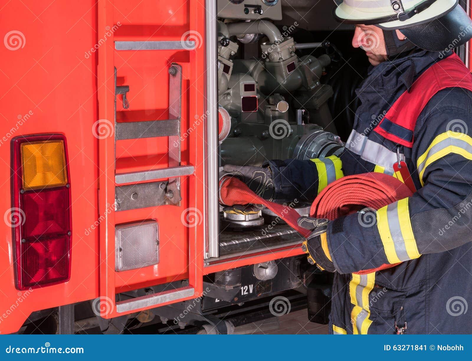 Strażak w akci łączył pożarniczego węża elastycznego na samochodzie strażackim