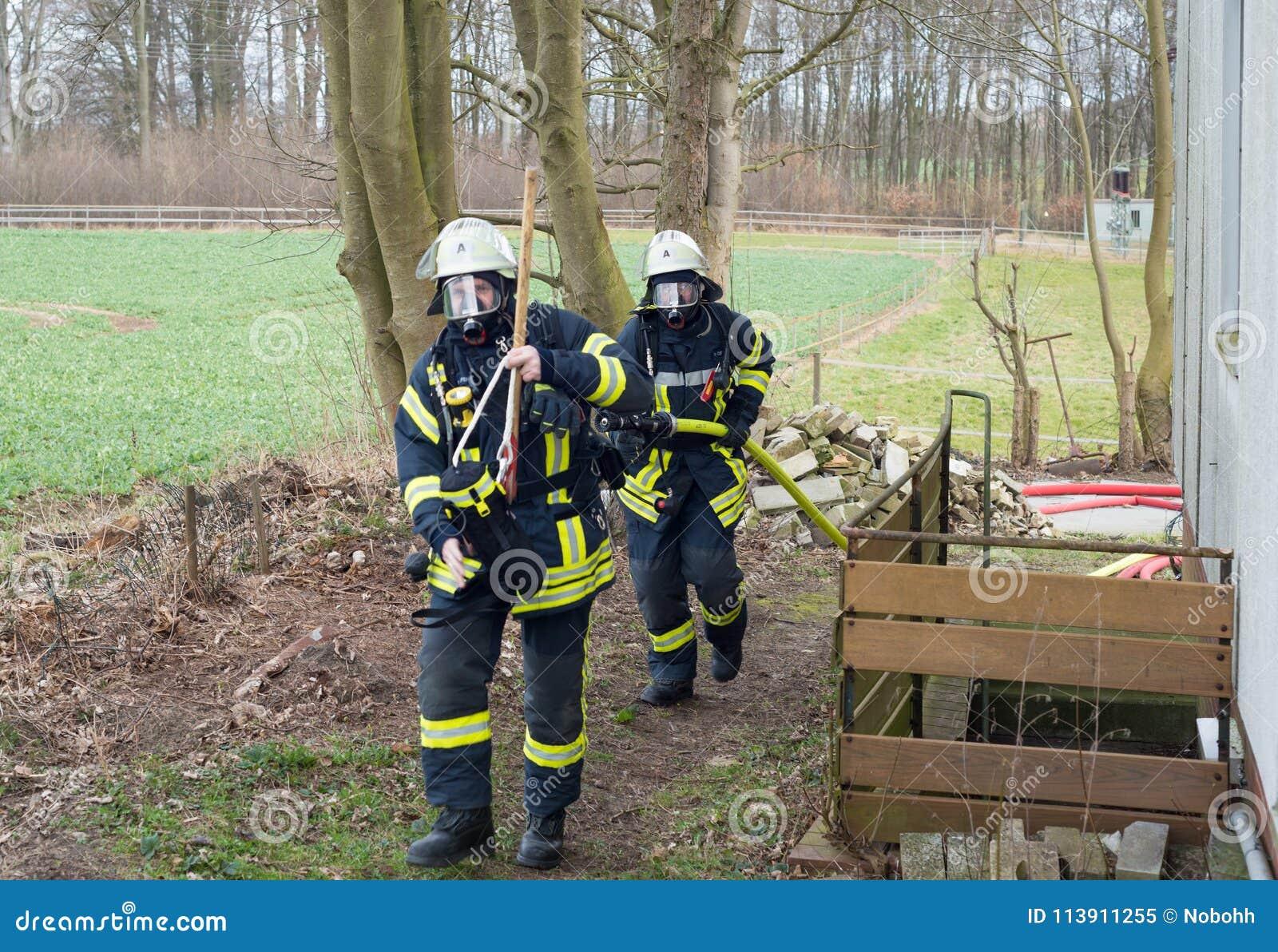 Strażak w akcji i gasi z pożarniczym wężem elastycznym - Seria strażak
