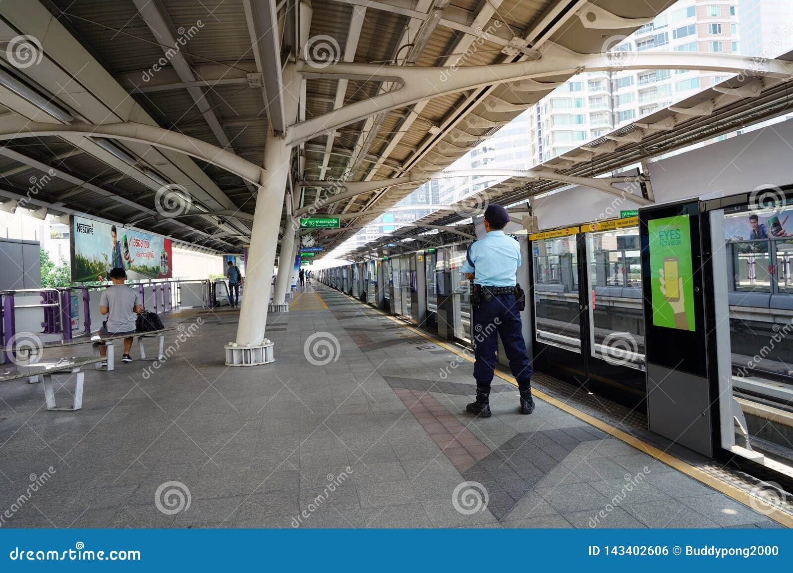 Strażowa ochrona czeka BTS skytrain przy stacją
