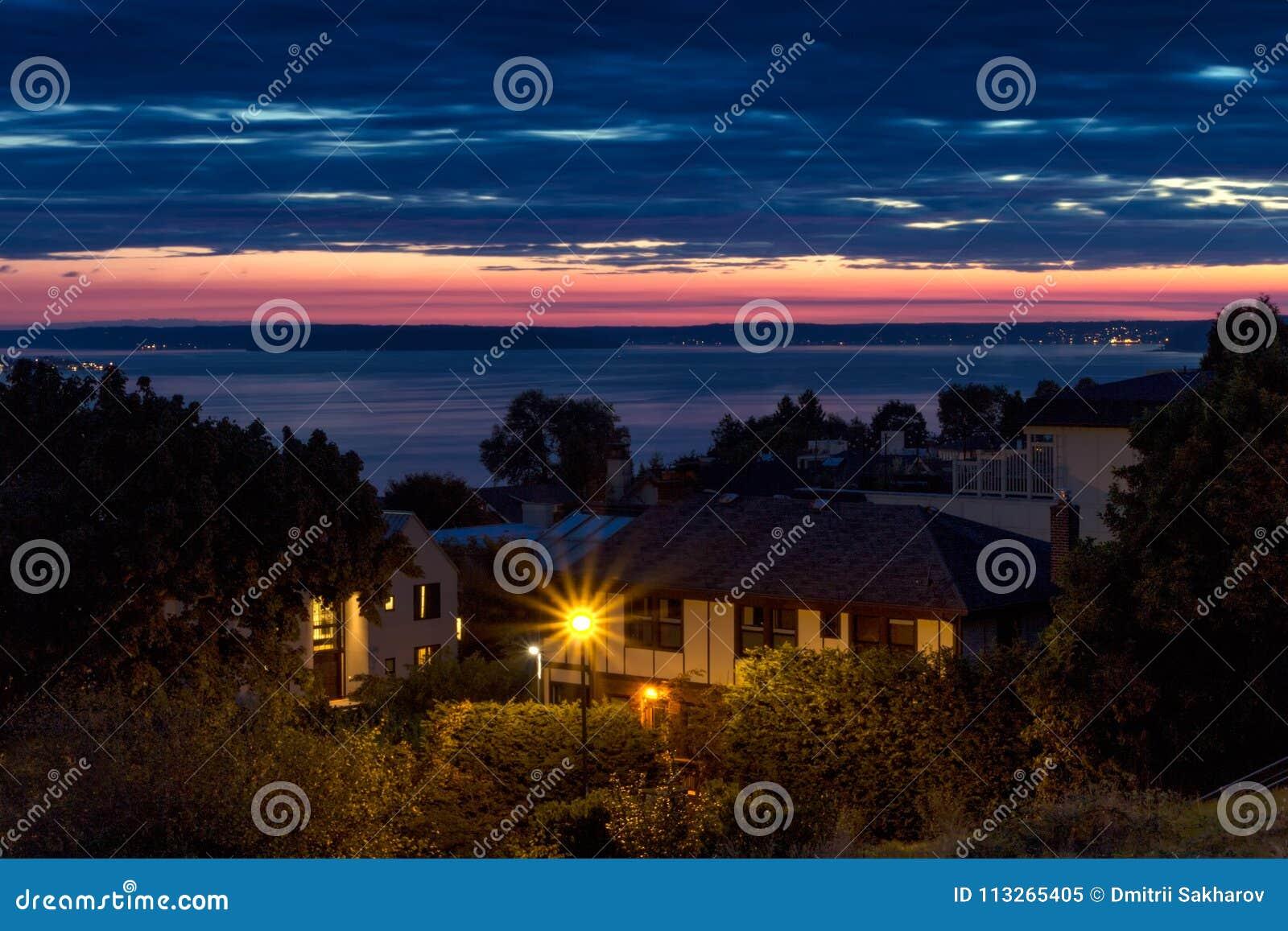 Straatlantaarn, huizen en overzeese mening bij zonsondergang in Seattle, de V.S.