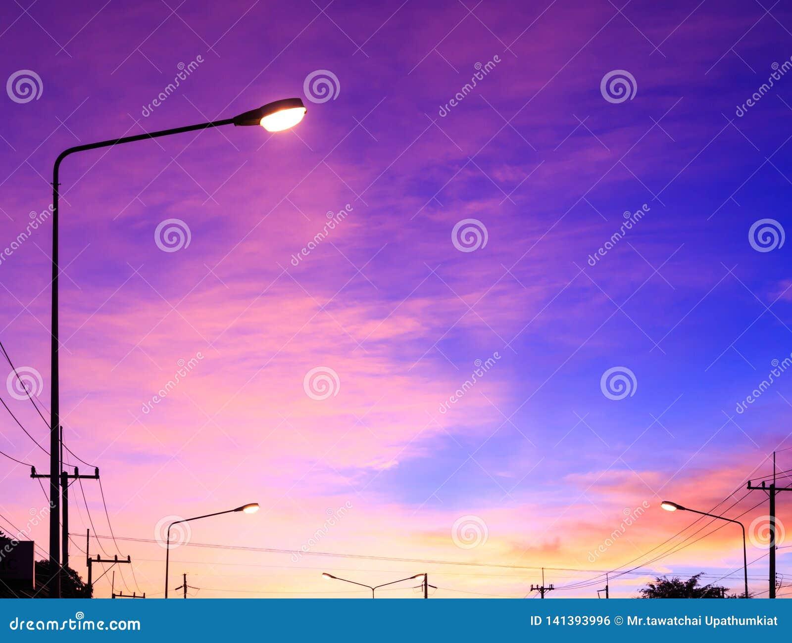 Straatlantaarn met hoogtepunt op de achtergrond van de fantasiehemel en roze wolken na zonsondergang