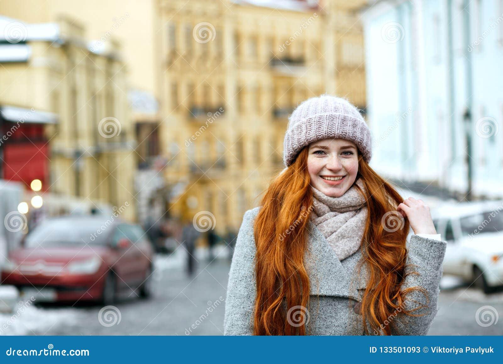 Straatportret van positief roodharigemodel met het lange haar dragen