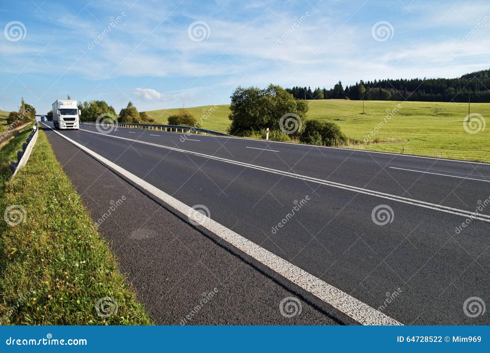 Strada asfaltata in un paesaggio rurale Il camion bianco arrivante sulla strada