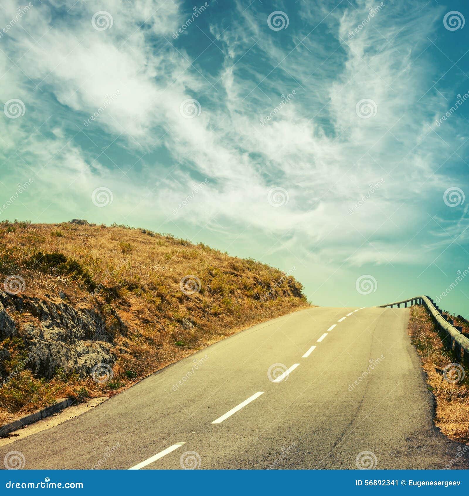 Strada asfaltata vuota e cielo nuvoloso